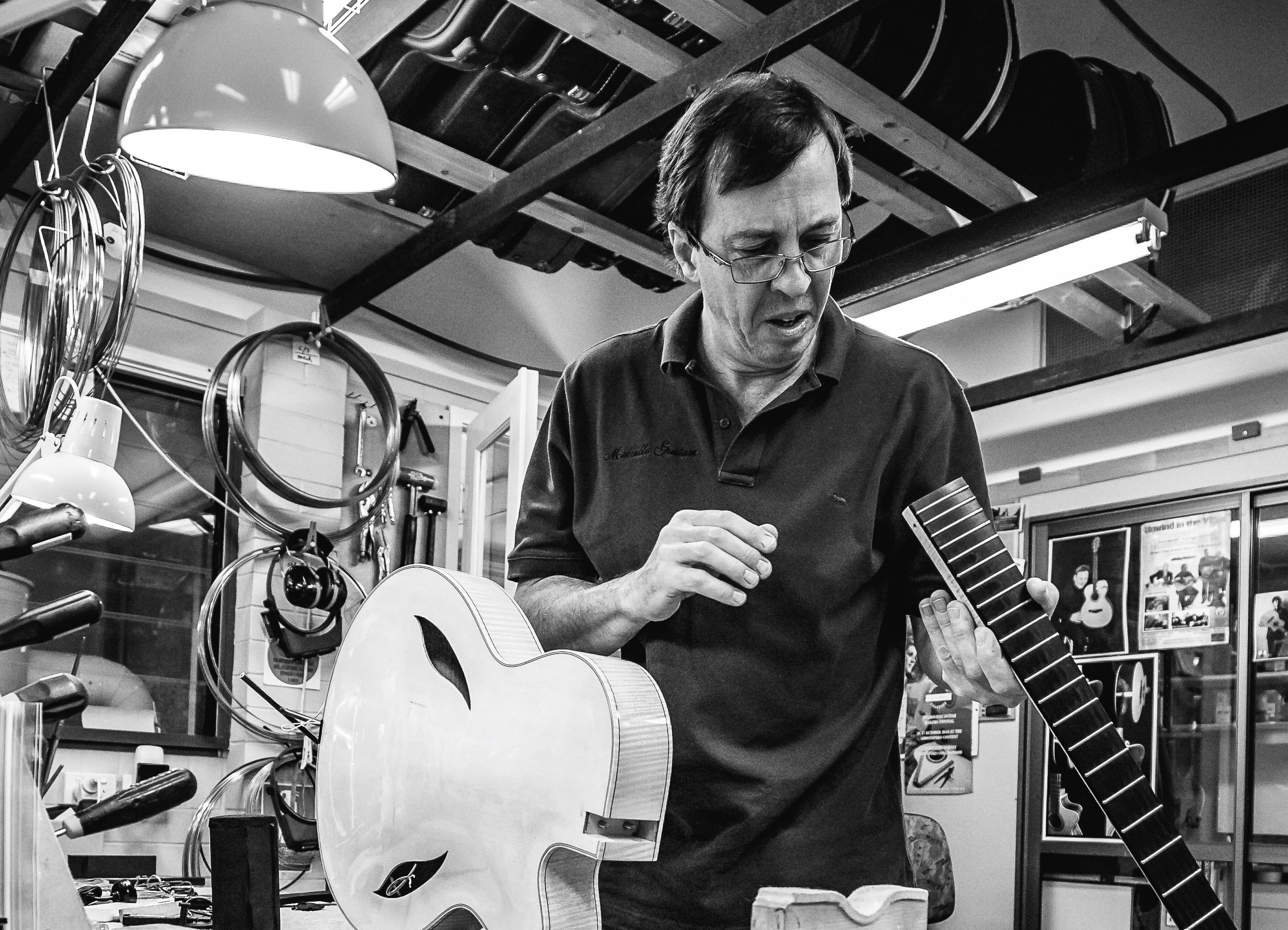 Chris Melville, guitar repairer in Brisbane, taking a neck off a guitar