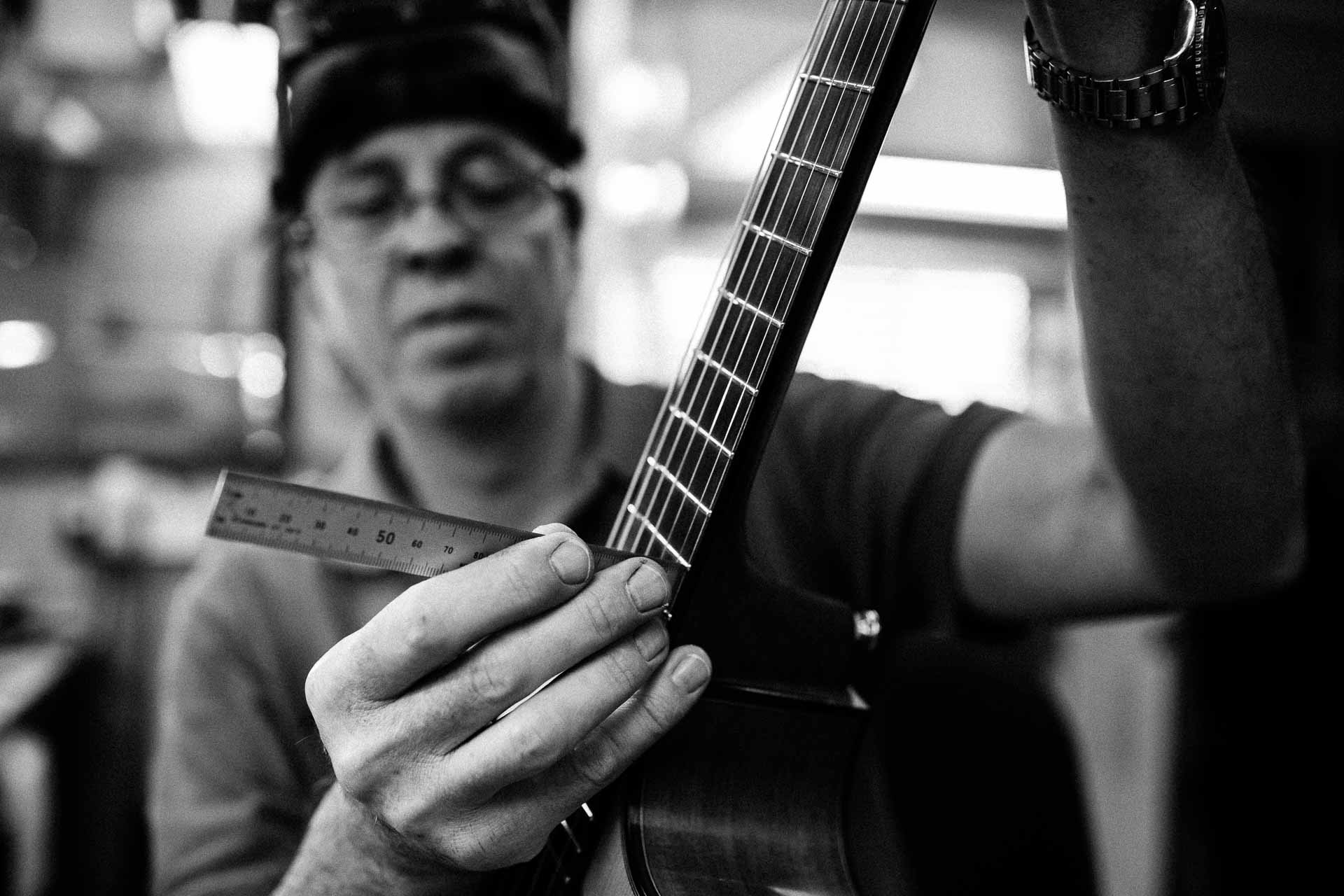 Chris Melville, guitar repairer in Brisbane, working on a guitar's frets